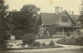 [An unidentified family and dog on the lawn in front of a house]