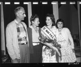 Carol Lucas, winner of Miss P.N.E. 1957, poses with group, likely her family