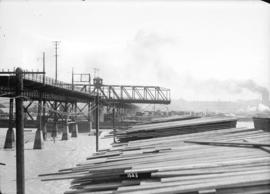 [Lumber piled near portion of Connaught Bridge (Cambie Street Bridge), damaged by fire]