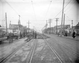 [Men excavating street and laying streetcar tracks on Fourth Avenue, looking east from Fir Street]