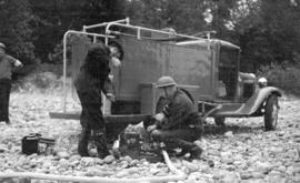 [Two A.R.P. firemen working on booster pump near fire wagon at Lynn Creek]