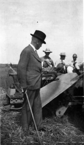 [Honourable K.C. MacDonald, Minister of Agriculture inspecting a fibre flax pulling machine]