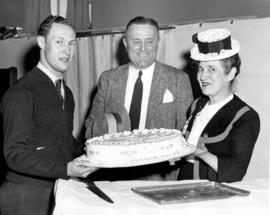 [H.J. Christison, Leo Sweeney and Miss Margaret McNeil admire a diamond jubilee cake at Shaughnes...