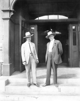 [L.D. Taylor standing with an unidentified man in front of a building]