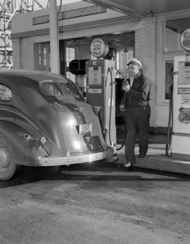 [Harry Howe's service station attendant at the pump ready to fill up a car]
