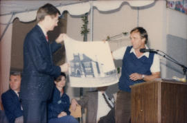 Two men holding up drawing at podium