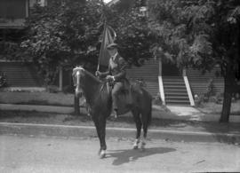 Man carrying a flag on a horse