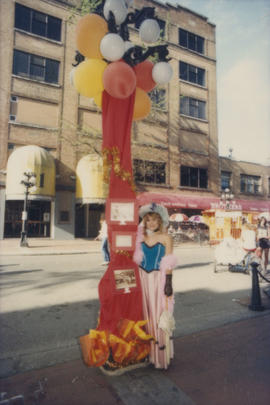 Woman wearing costume standing next to decorated lamp post