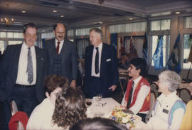 [Ted Allan], Mike Harcourt and unidentified man speaking with table of attendees