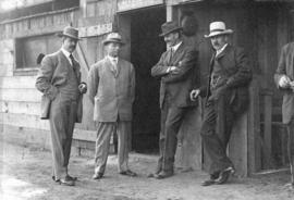 [L.D. Taylor standing with three men at sports field]