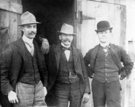 [Three unidentified men standing outside of a building]