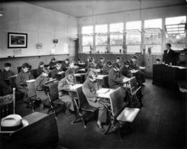 Children seated at desks wearing coats in classroom at Open Air School