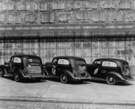 Three parked cars bearing advertisements for canned salmon, T.A. James Specialty Corp.