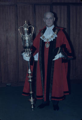 W.O. B[anfield] in mayor's robes standing with mace