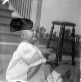 [Theodore Taylor sitting on sidewalk in front of house at] 14 mo[nths]