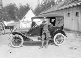 68th Canadian Field Artillery [soldier standing beside car]