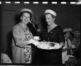 P.N.E. director and woman with platter of food at tea party