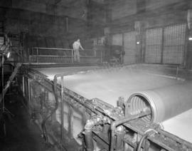 [A man operating a] paper machine [at] Pacific Mills