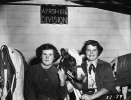 Girls posing with Ayrshire calf in Livestock building