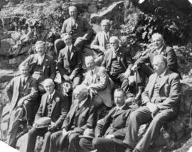 [Mayor L.D. Taylor sitting with eleven men on rocky slope]