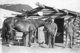 Men and horse in front of log blacksmith's shop during the Klondike Gold Rush