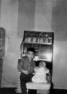Vernon Yee with his younger brother Paul by the jukebox in their father's café in Naicam, Sa...