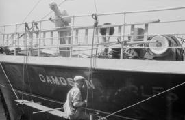"[Man painting the hull of the S.S. ""Camosun""]"