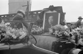 [Portrait of man on car decorated with flowers for funeral procession]