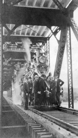 [Men standing on the front of a locomotive on the bridge]