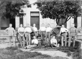[Soldiers with machinery outside brick building]