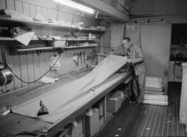 Wing Hing Dry Goods Ltd. owner Lin Bei-lian at workbench with textile fabric