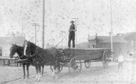 [A horse-drawn lumber wagon at the corner of Hastings Street and Cambie Street]