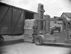 [Man operating a forklift at Evans, Coleman, and Evans, Ltd., lifting a load into a railway car]