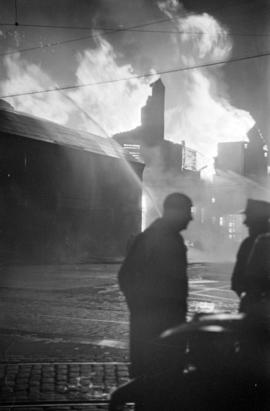 Denman Arena fire with silhouettes of two men in the foreground
