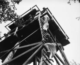 Liquor Board picnic [picnickers climbing water tower, possibly Bowen Island]