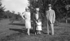 [Young child outdoors with two women and a man]
