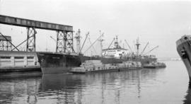 S.S. Seafair [at dock, with lumber-filled barges alongside]