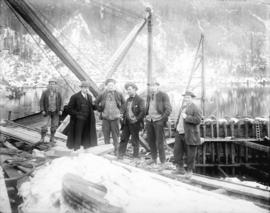 [Six men standing at location of intake gate of hydraulic tunnel for Buntzen Lake Power Plant num...