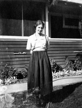 Miss Marion Pierce [standing in front of a house]