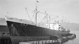 M.S. Ume Maru [at dock, with lumber-filled barges alongside]