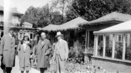 [Three men and a woman standing in front of some buildings at Butchart Gardens]