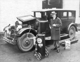 [L.D. Taylor standing next to car into which is being pumped material from a cannister labelled N...