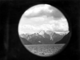 "[View across Kwatna Inlet off Burke Channel through a porthole of S.S. ""Cardena""]"