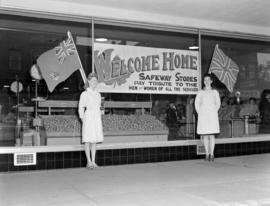 [Women standing on either side of a banner in a Safeway Store window paying tribute to the men an...