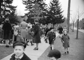 [Children and teachers gathered on sidewalk as part of an air raid drill]