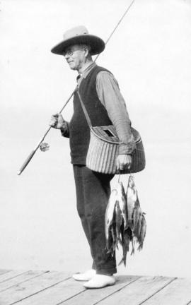 [L.D. Taylor carrying a fishing pole, fishing basket and several fish on a string]