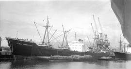 M.S. Klaus Leonhardt [at dock, with lumber-filled barges alongside]