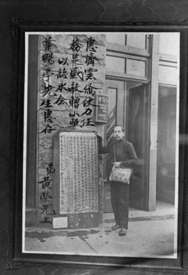 Man standing next to a banner and sign outside the Wing Sang Company building at 51 East Pender S...