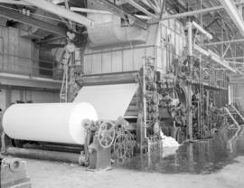 [View of the Westminster Paper Company plant showing a large roll of paper a the end of a row of ...