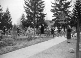 [Children leaving school on bicycles as part of an air raid drill]